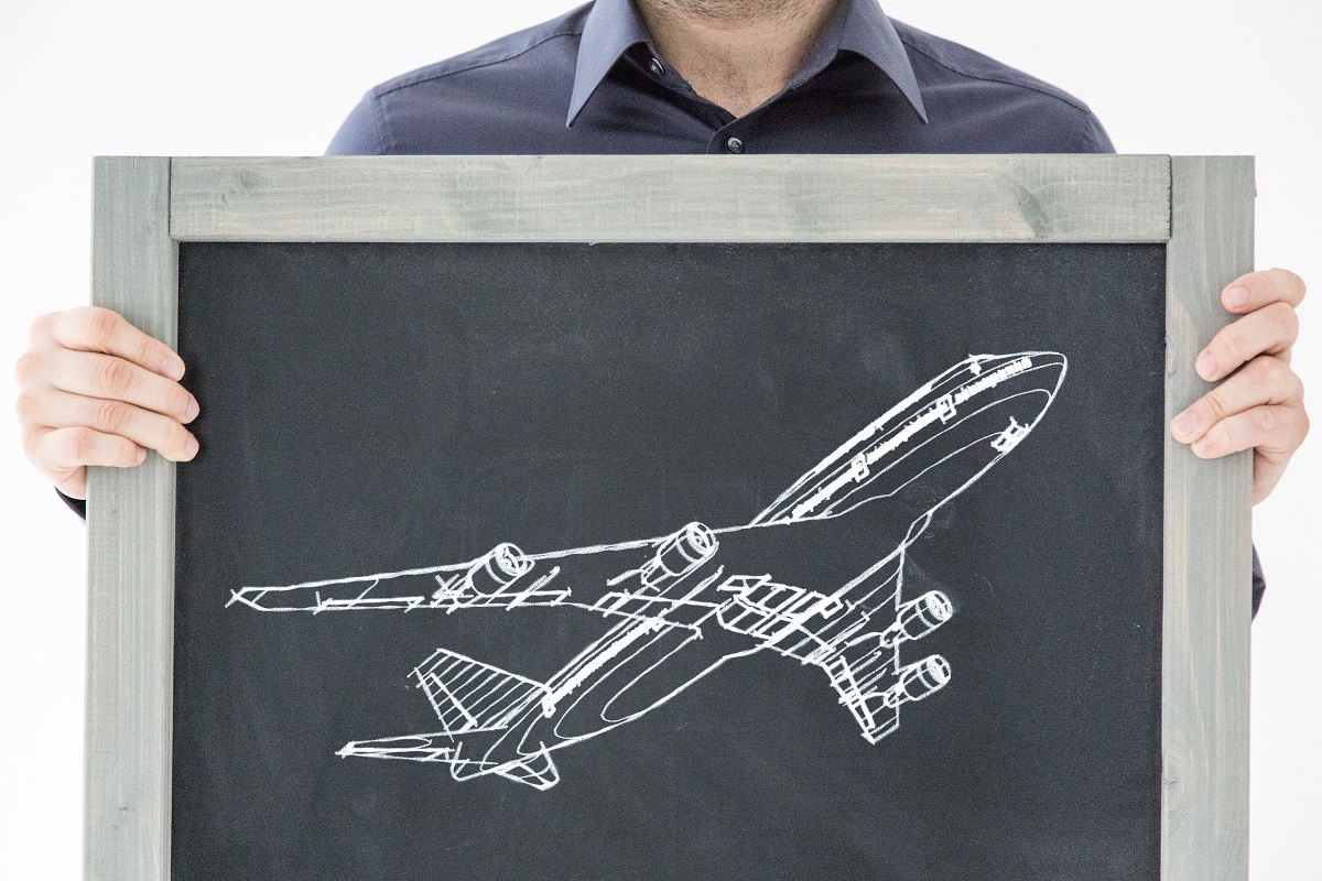 man holding chalkboard with airplane sketch