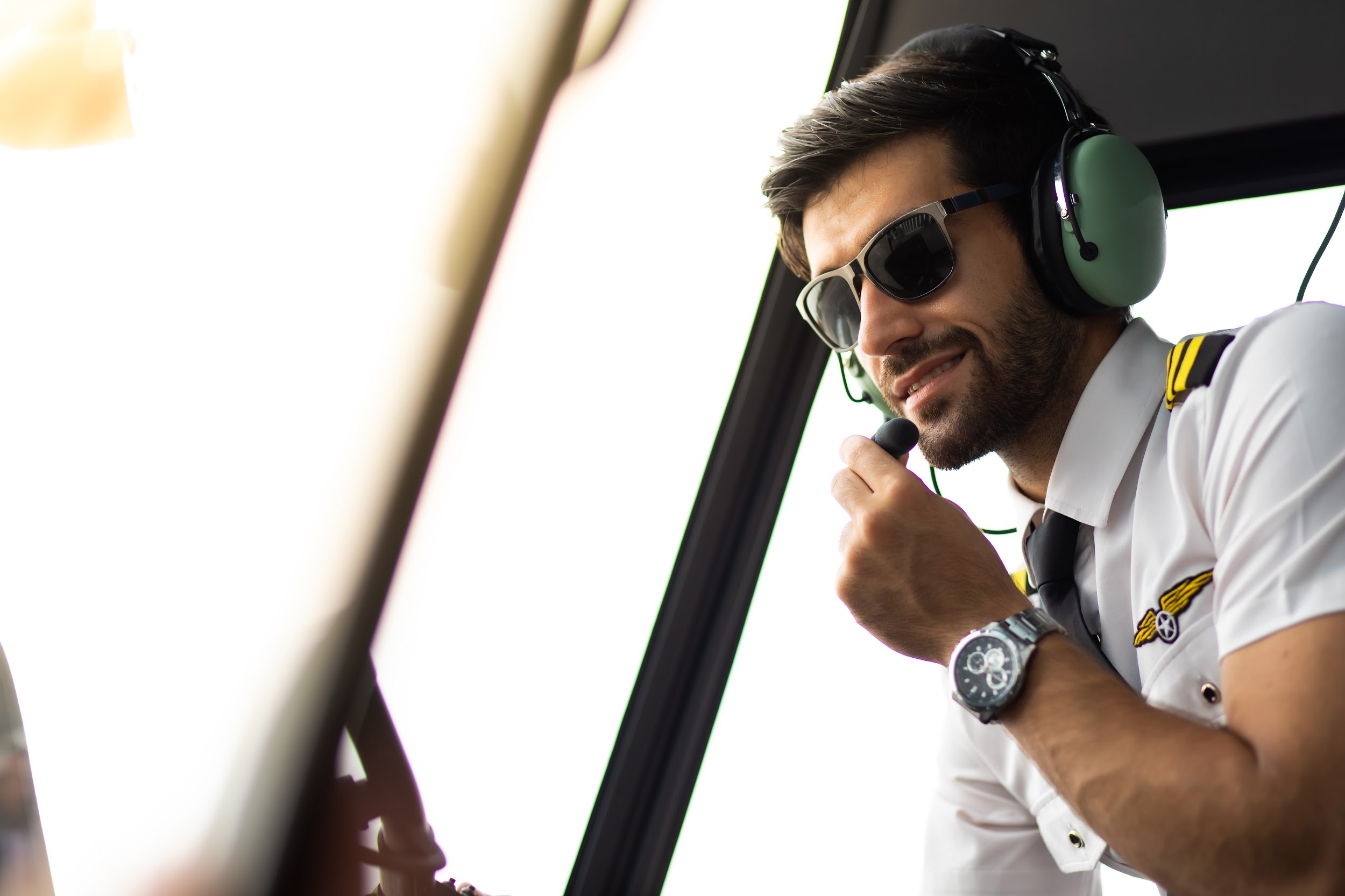 pilot with headset starting the controls in cockpit helicopter