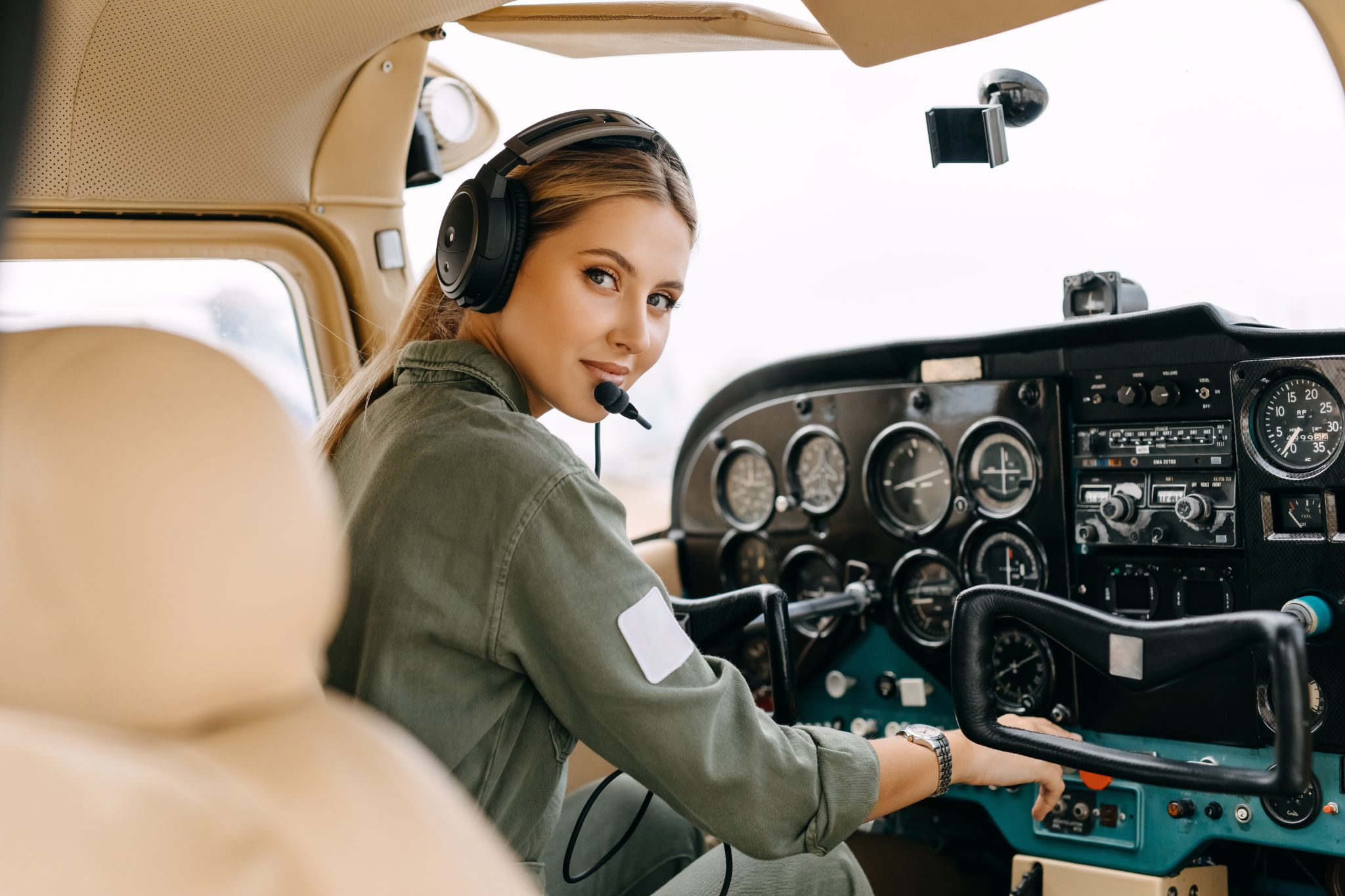 Woman pilot sitting in private airplane cockpit