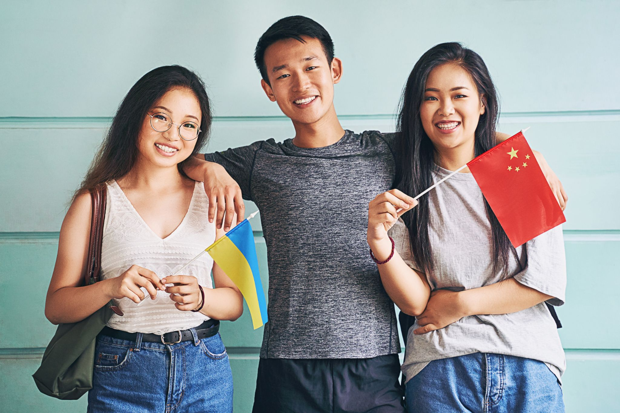 Group of three asian students smiling and holding flags of China and Ukraine
