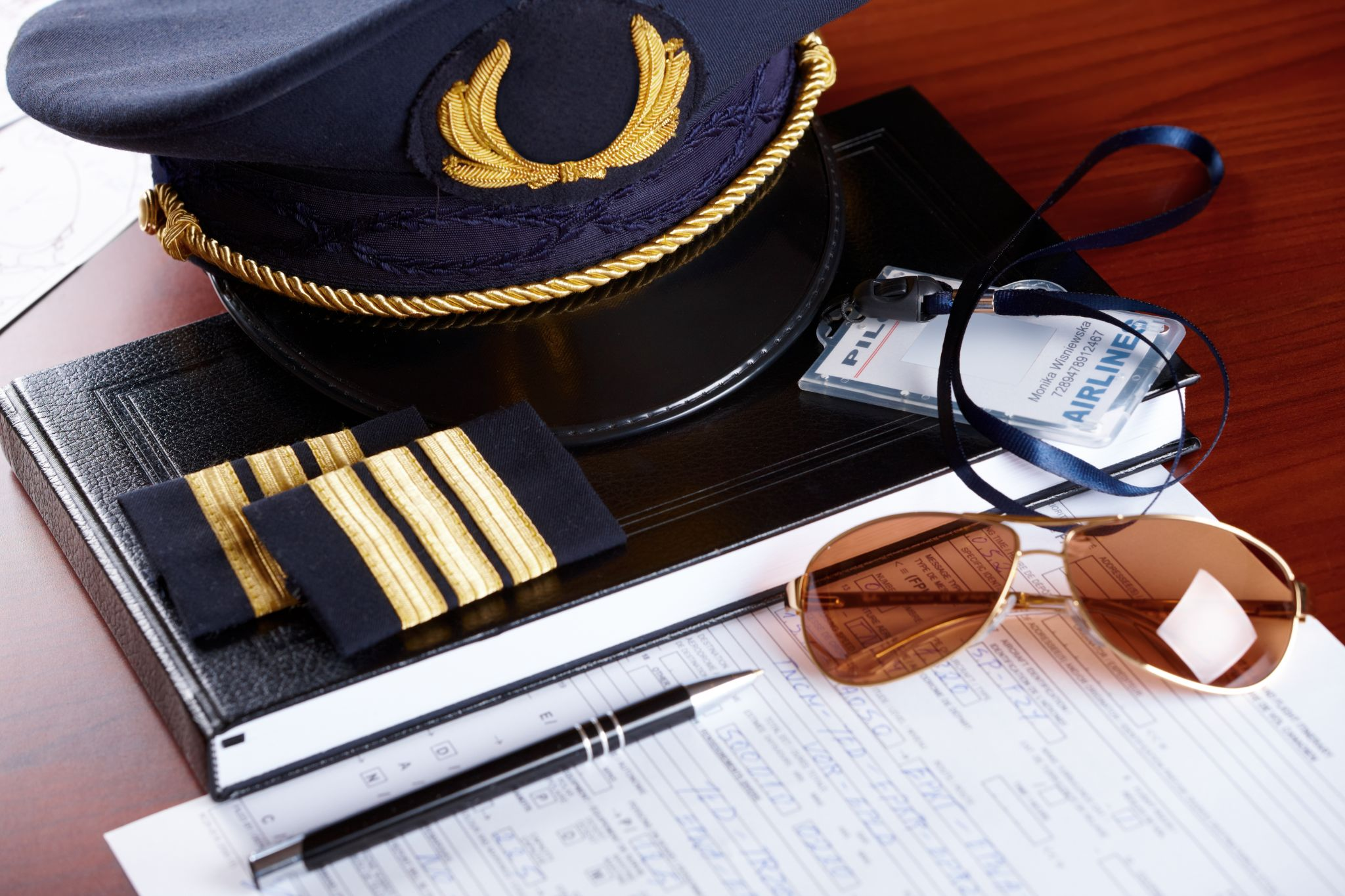pilot hat and id holder with epaulets and sun glasses laying on log book and flight plan.